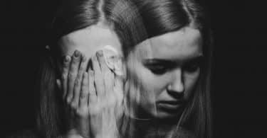Figura de mulher em dois planos: à frente, ela está com as mãos sobre o rosto; sob esta imagem, ela está cabisbaixa.