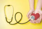 Estetoscópio em um fundo amarelo sobre um coração vermelho