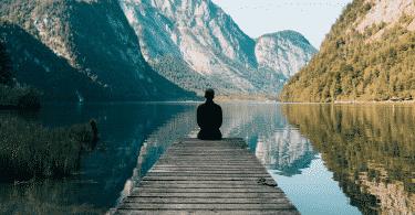 Homem sentado no deck observando o lago