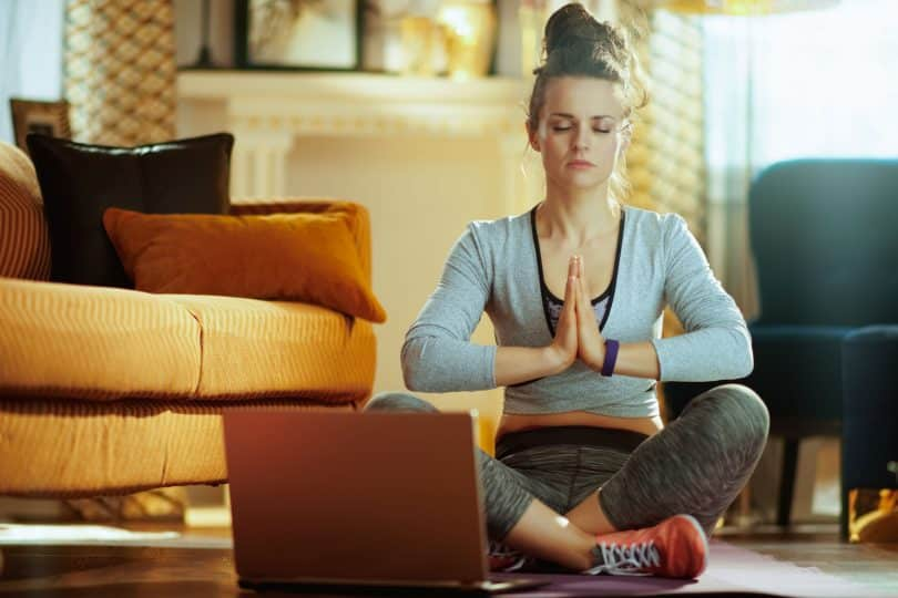 Mulher com roupas de academia sentada no chão de uma casa meditando usando o laptop