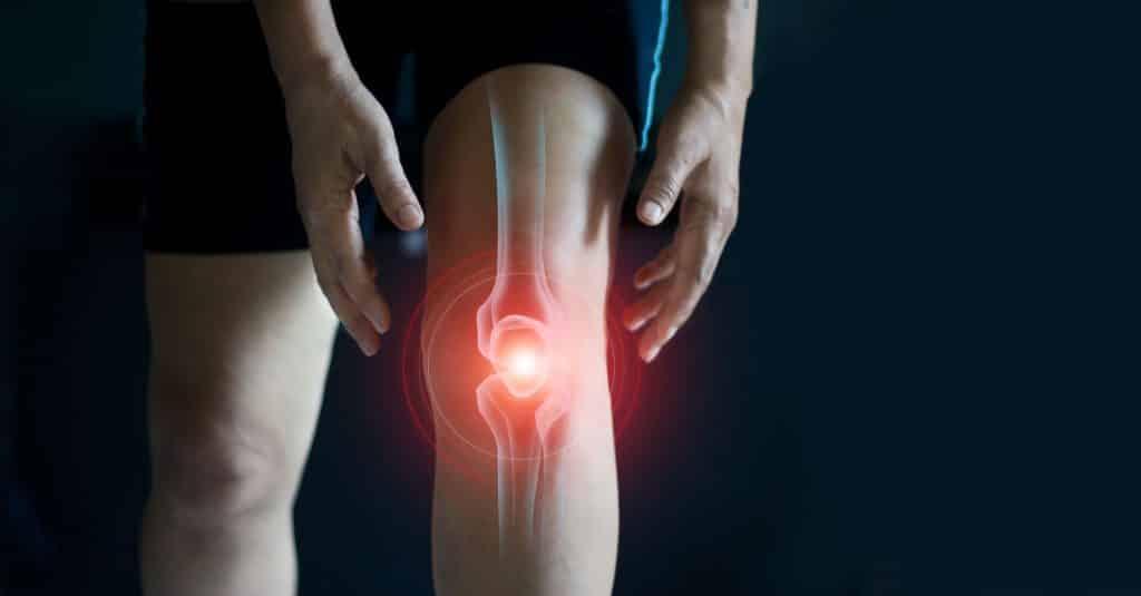 Indicação de dor no joelho de pessoa branca.