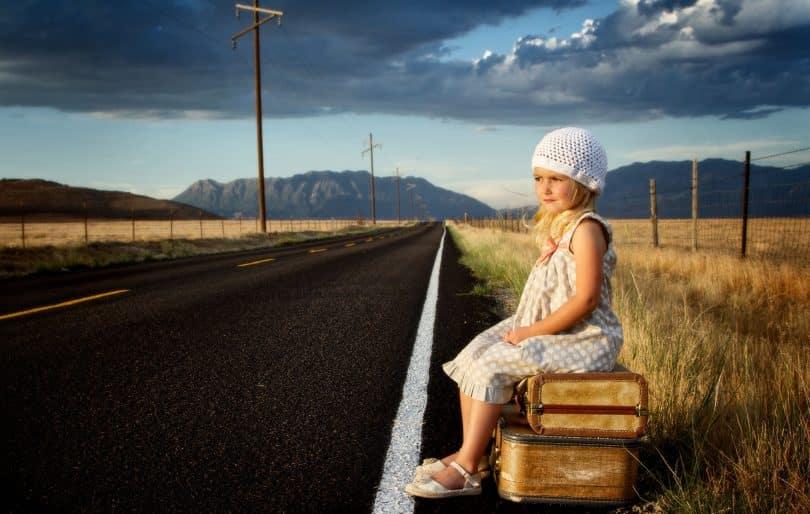 Menina à beira da estrada sentada sobre duas malas.