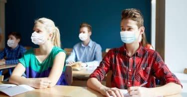 Grupo de estudantes com máscaras. Eles estão em uma sala de aula, sentados à mesa, que contém cadernos e livros.