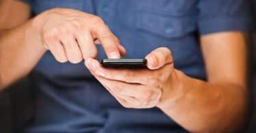 Pessoa mexe em celular.