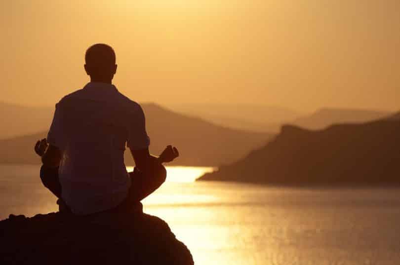 Homem medita sobre pedra. Ao fundo, há o mar, montanhas e o cenário é de pôr do sol.
