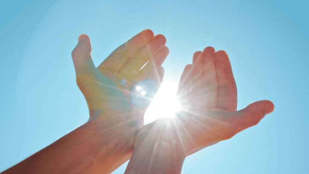 Mãos juntas erguidas para o sol