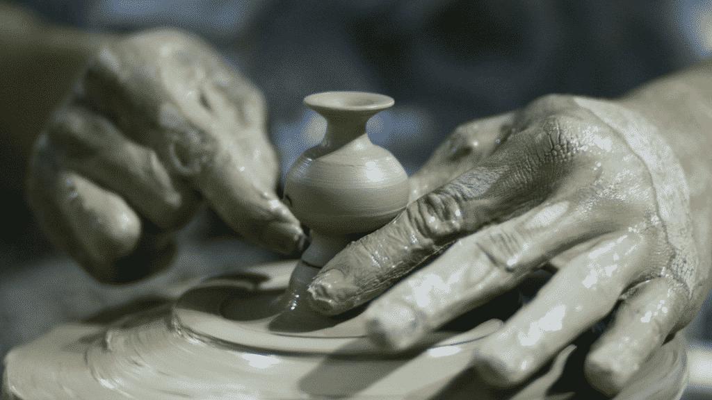 Homem fazendo cerâmica com argila