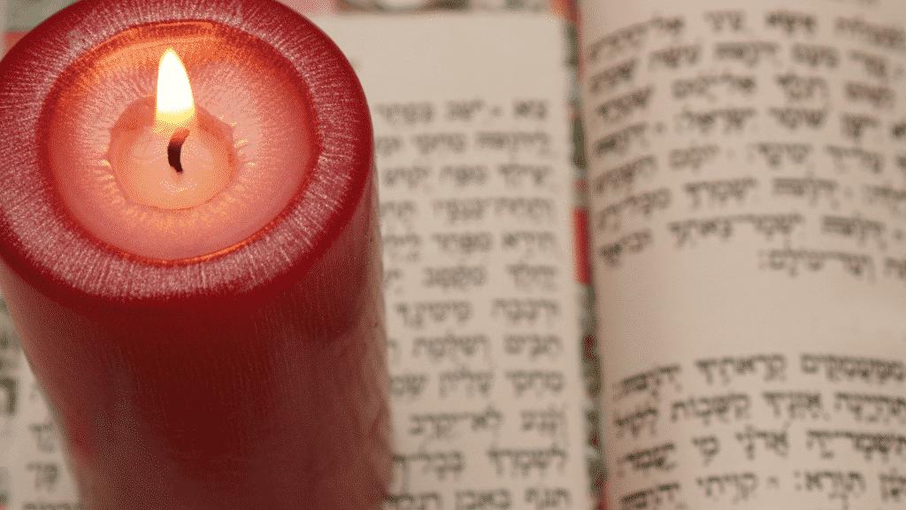 Livro sagrado judaico aberto para estudo da cabala com vela vermelha acesa ao lado