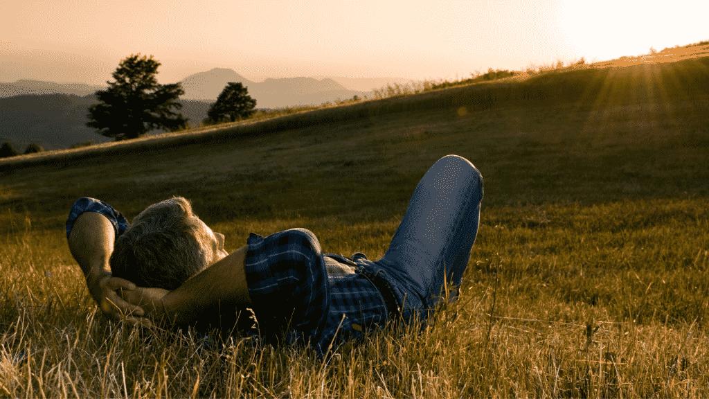 Homem deitado na grama observando o pôr do sol