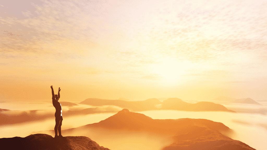 Pessoa no pico de uma montanha com os braços erguidos