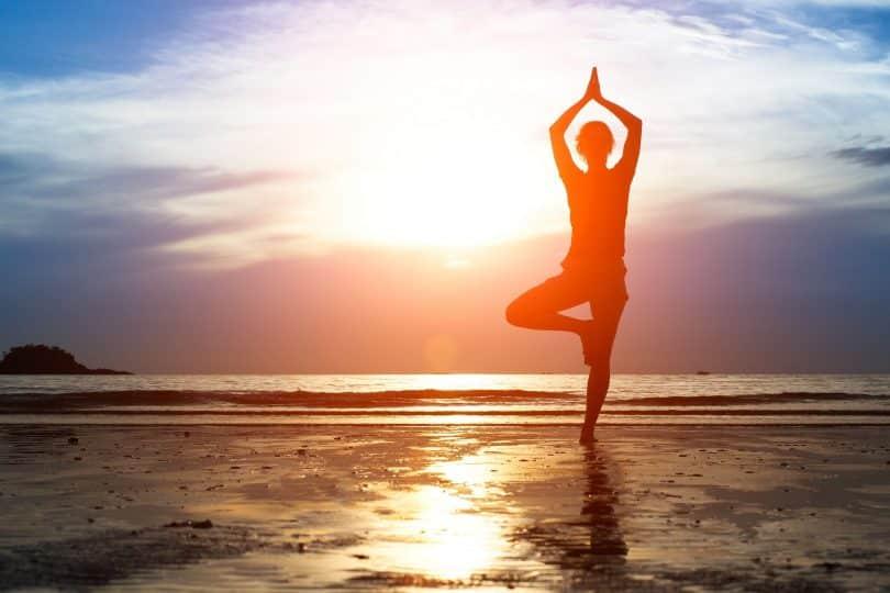 Mulher praticando yoga na praia.