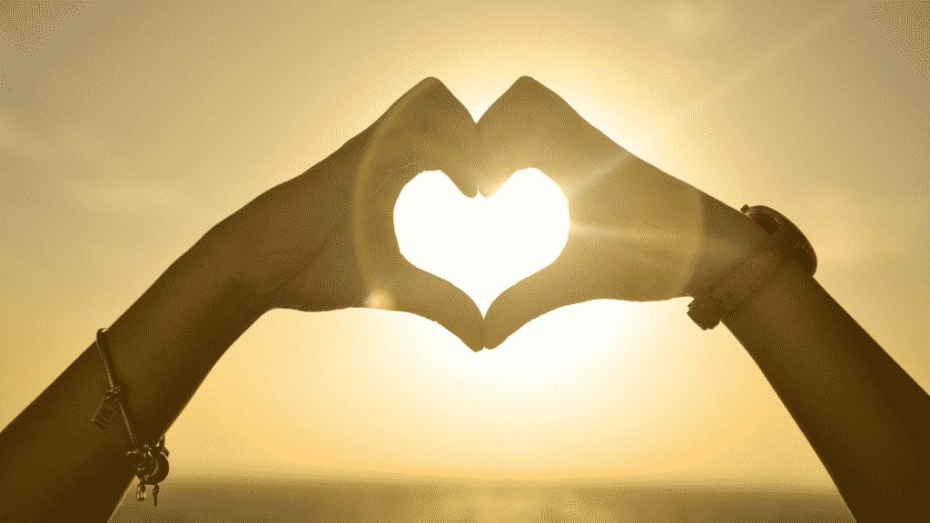 Casal fazendo um coração com as mãos