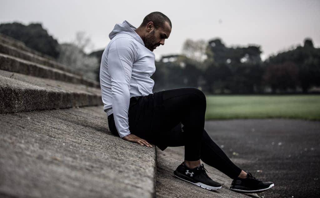 Homem branco usando roupas de ginástica, sentado no concreto.