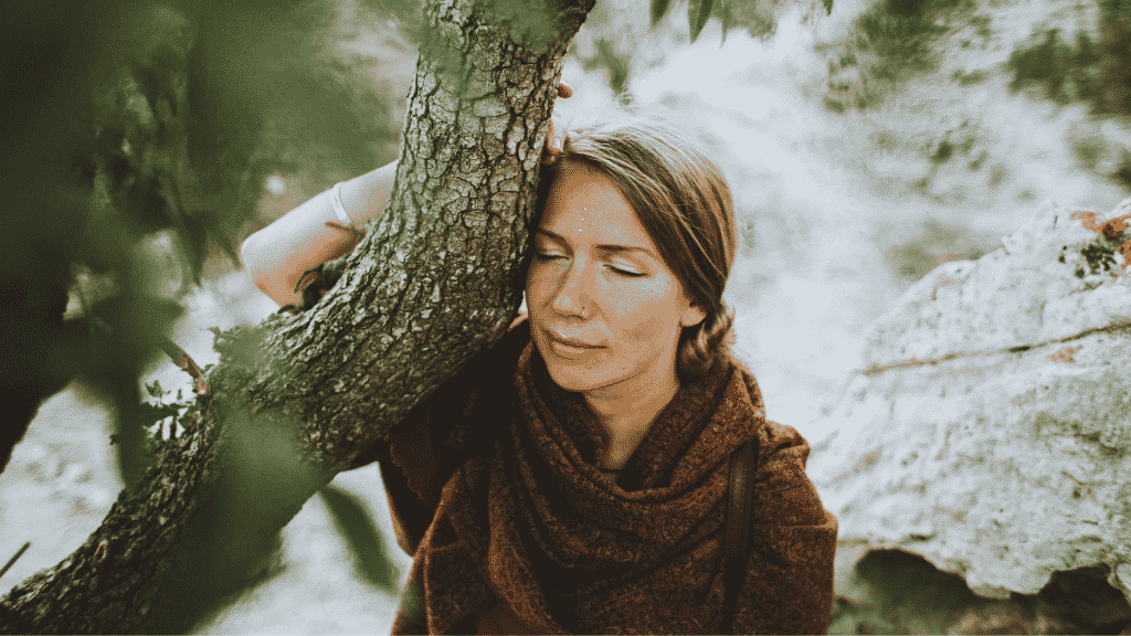 Mulher pensativa abraçada na árvore