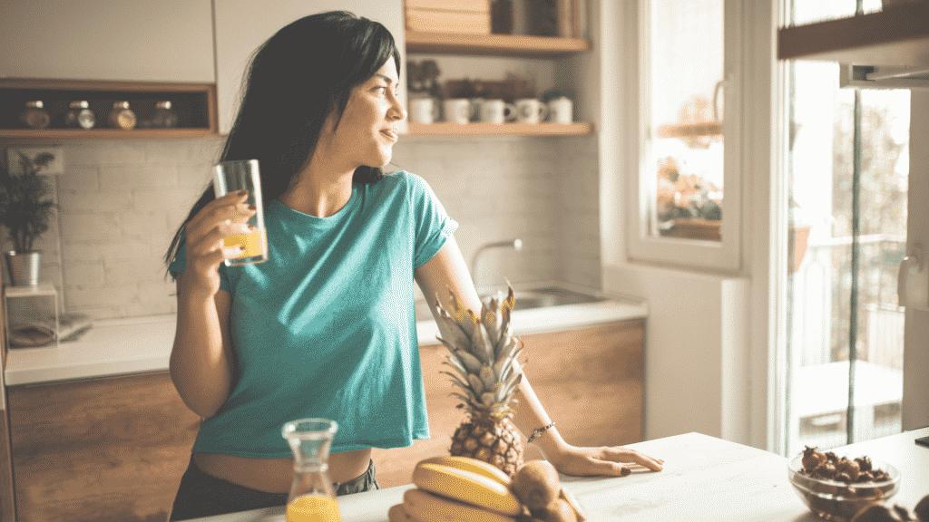 Mulher feliz tomando suco de manhã