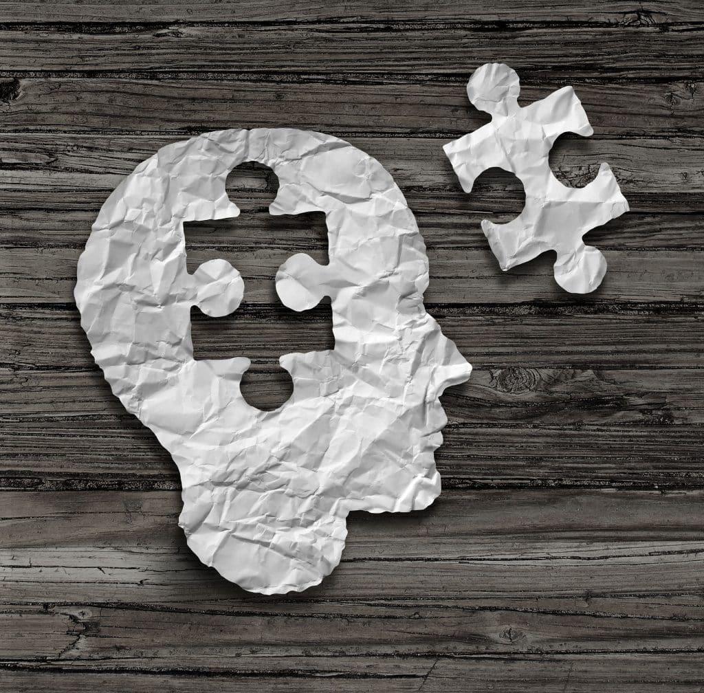 Um perfil de rosto humano feito de papel branco amassado com um pedaço de quebra-cabeça recortado