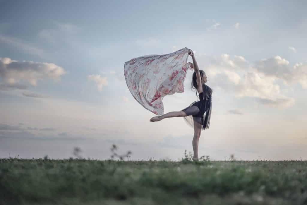 Mulher branca dançando num campo, enquanto segura lenço florido.