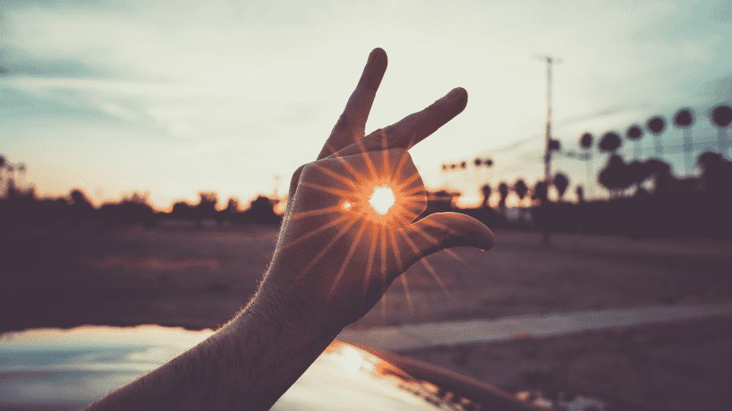 Mão fechada sobre o sol para representar perspectiva