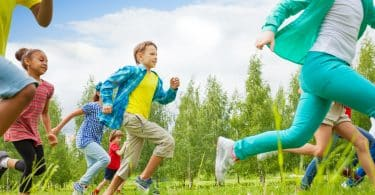 Crianças correm em meio a gramado.