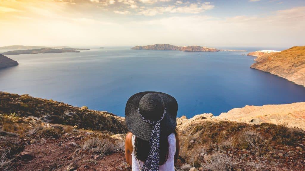 Mulher sentada de costas num morro com mar à frente.