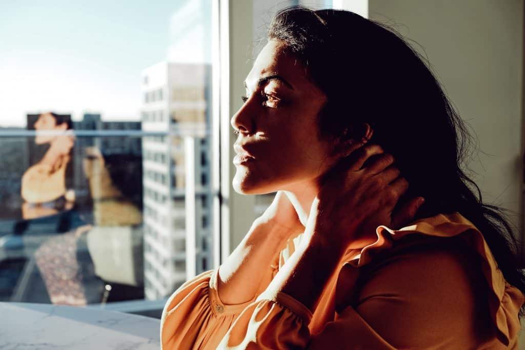 Mulher branca com as mãos no pescoço e rosto iluminado pelo Sol.