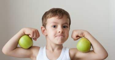 Menino branco com maçãs verdes nos braços.