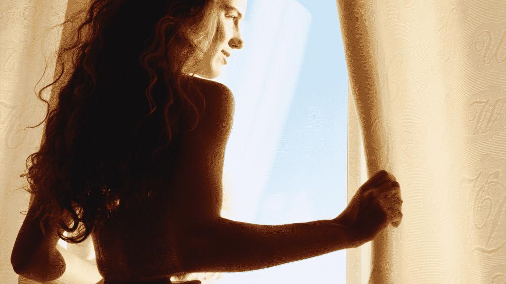 Mulher sorridente abrindo a cortina e olhando pela janela