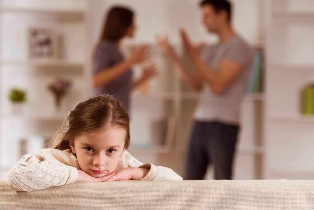 Criança branca com expressão triste enquanto os pais brigam atrás.