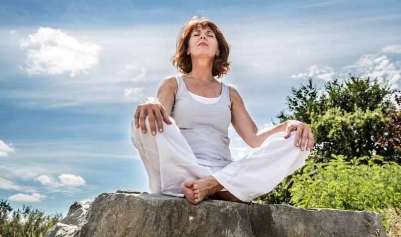 Mulher branca sentada num tronco de árvore com os olhos fechados.