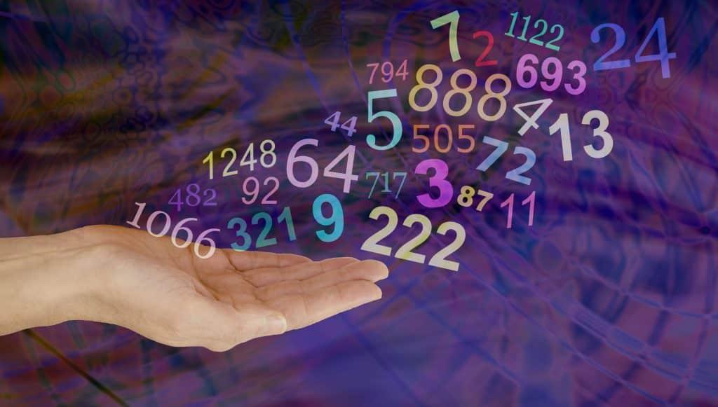Números sobre mão feminina. O fundo é abstrato e roxo.