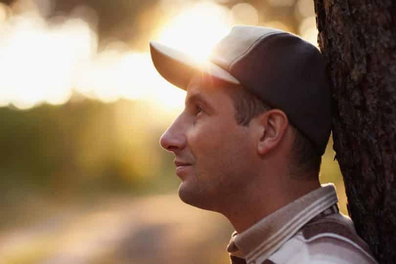 Perfil de homem branco usando boné.