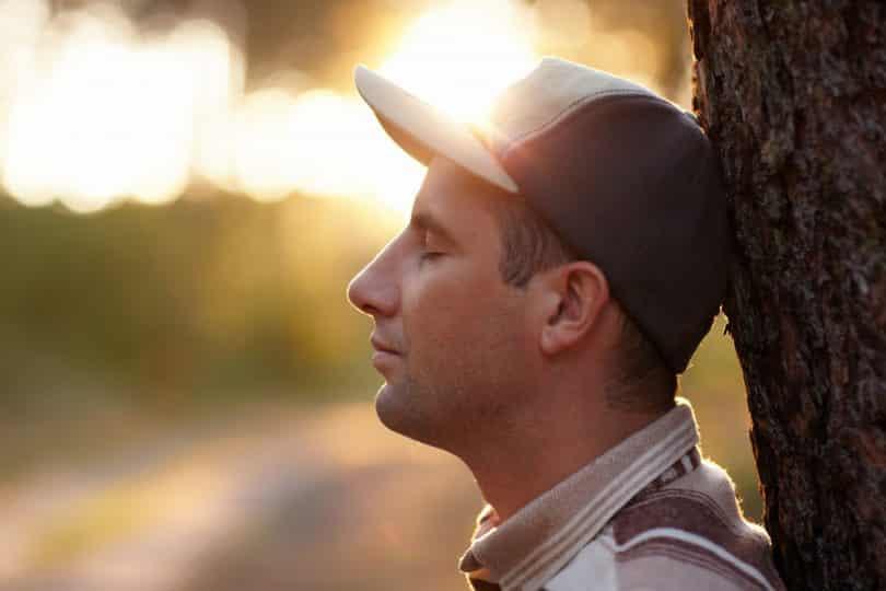 Foto de perfil de um homem com os olhos fechados e encostado em uma árvore.