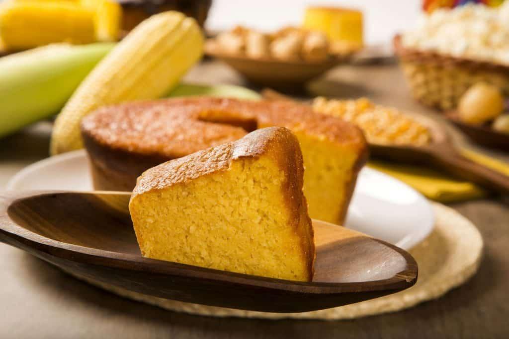 Fatia de bolo de milho cortada à frente do bolo em si. Ao fundo, há espigas de milhos e outros alimentos.