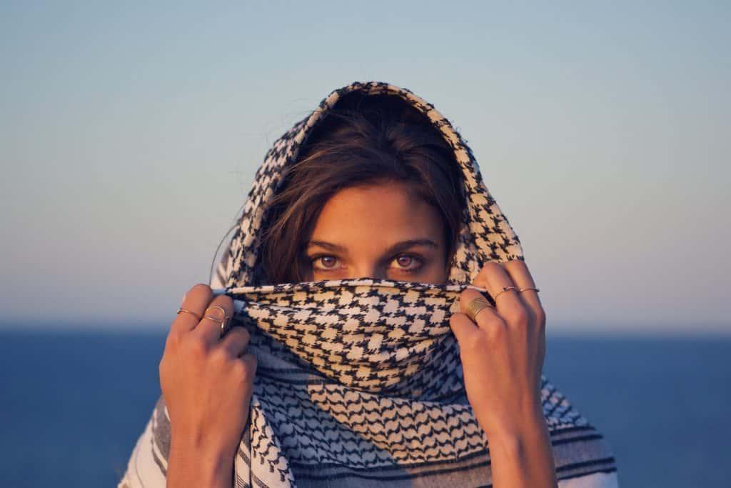 Mulher branca com lenço enrolado na cabeça com os olhos para fora.