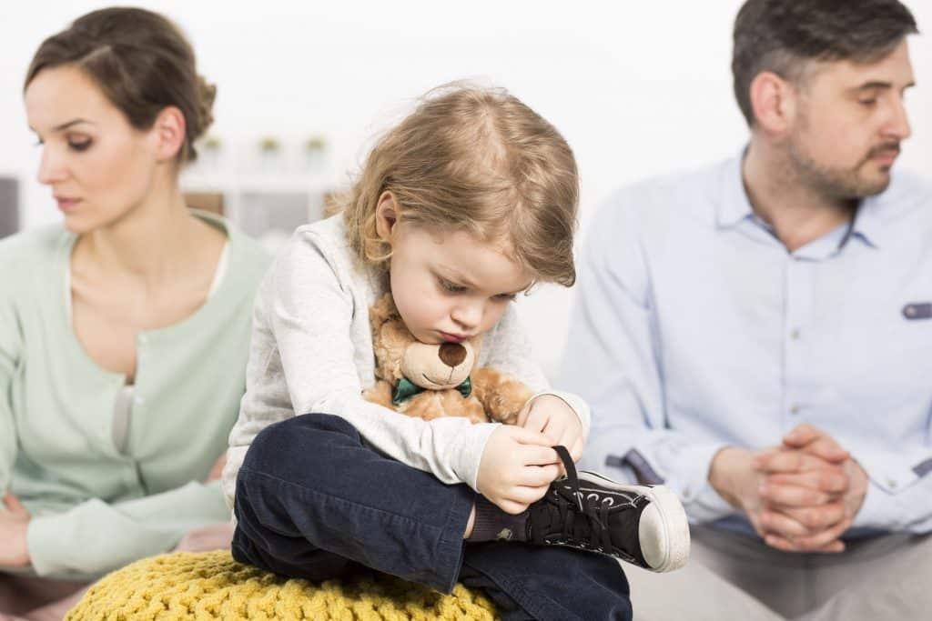 Criança branca com expressão triste e os pais com expressões sérias atrás.