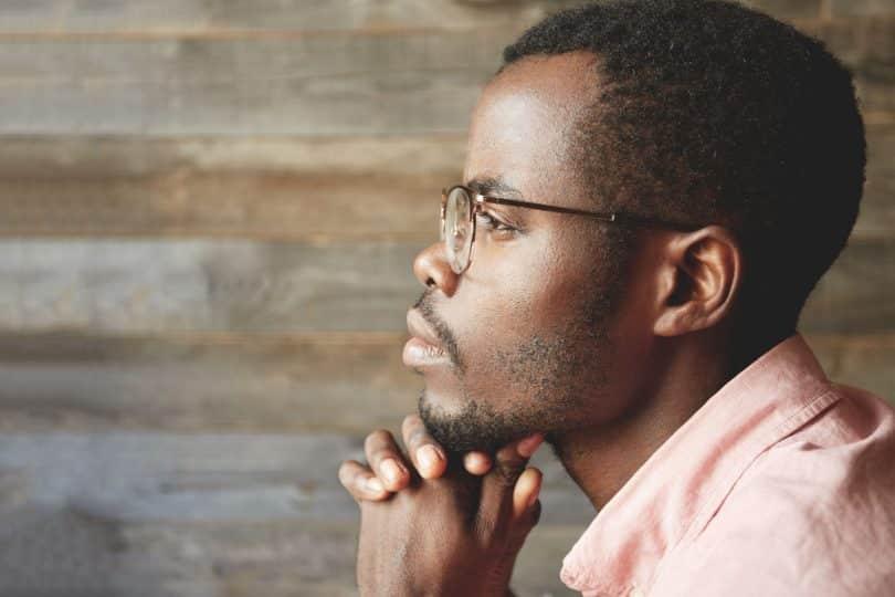 Homem jovem visto de perfil observa o horizonte. Ele apoia o queixo sobre as duas mãos unidas. O fundo é de madeira.