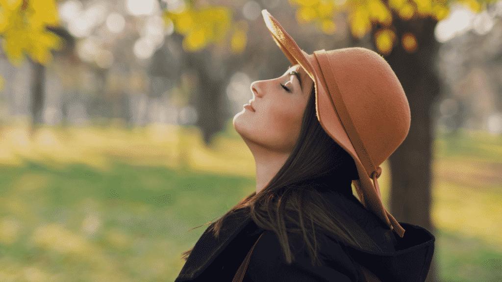 Mulher sorrindo de olhos fechados respirando fundo