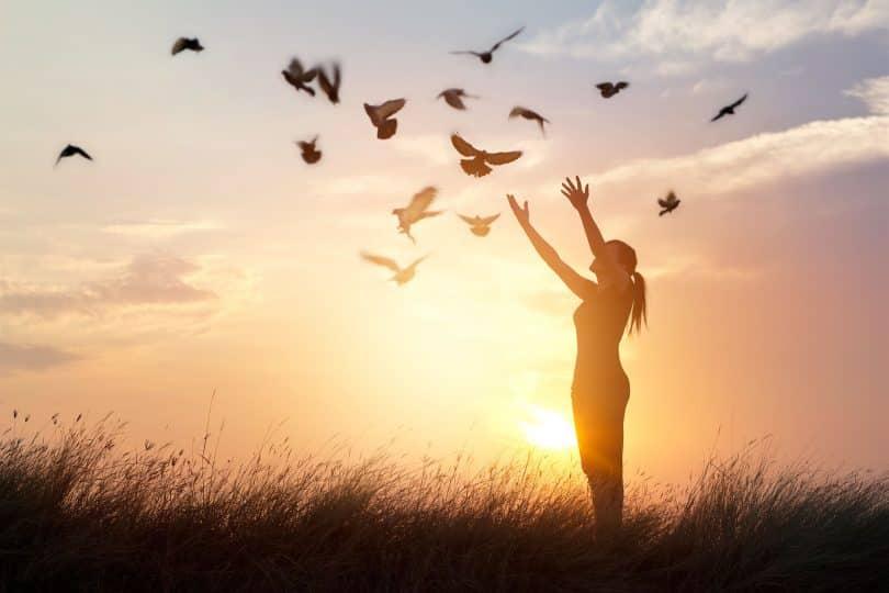 Mulher em cenário externo com os braços erguidos. Ao alto, há pássaros.