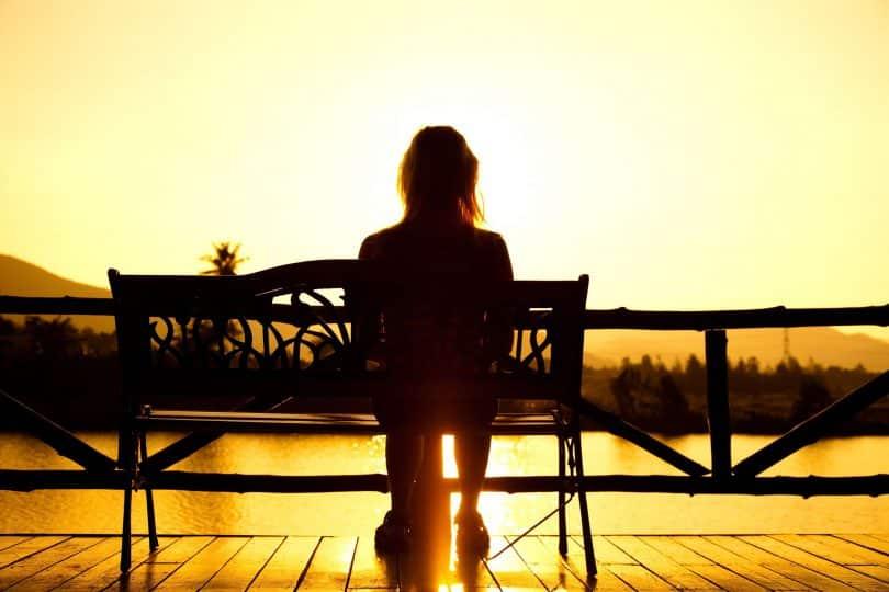 Mulher sentada em banco assiste ao pôr do sol.