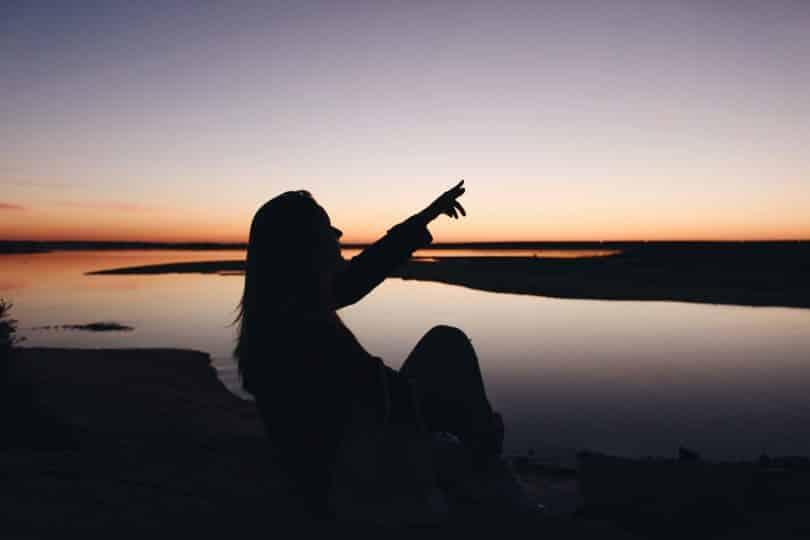 Silhueta de mulher sentada próximo ao lago num por-do-sol.