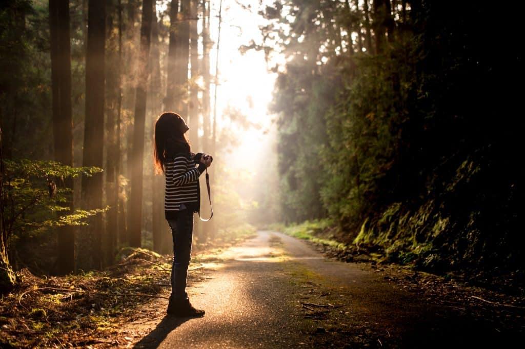 Mulher numa estrada no meio da floresta.