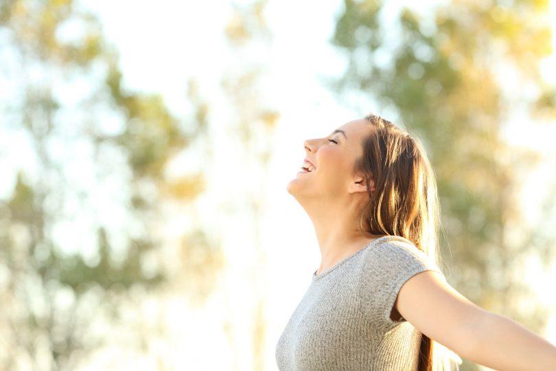 Mulher com os braços erguidos e abertos. Ela sorri e inclina a cabeça para trás.