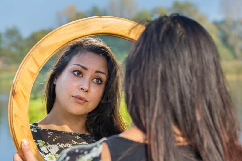 Mulher em ambiente externo se olha em espelho.