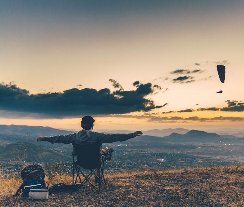Homem sentado numa cadeira no topo de um morro.