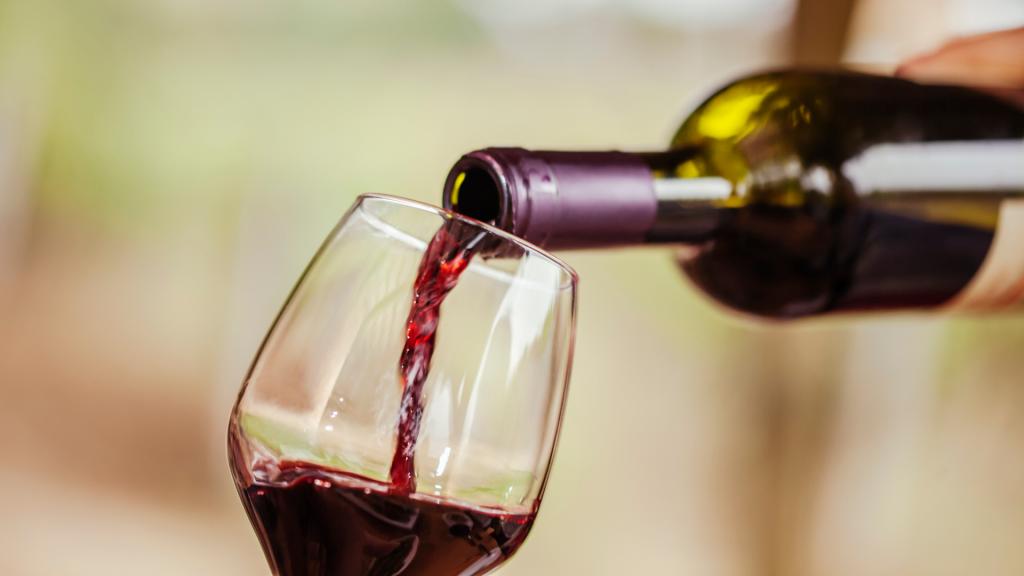 Pessoa colocando vinho em uma taça