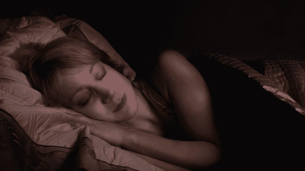 Imagem de uma mulher deitada na cama, dormindo