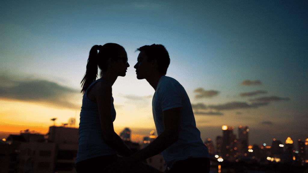 Imagem de um casal se beijando no terraço de um prédio