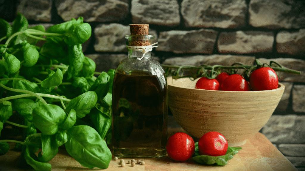 Imagem de manjericão, azeite e tomates em uma mesa