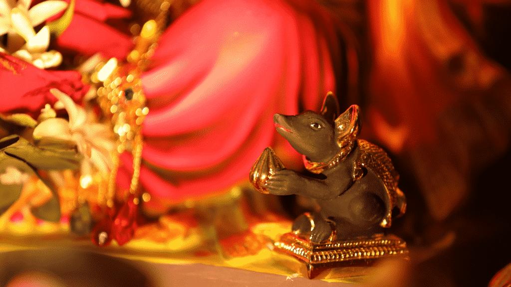 Imagem do rato, ao lado da estátua do Deus Ganesha
