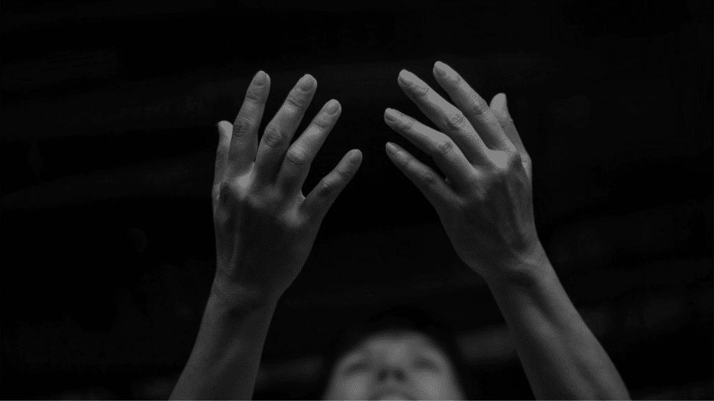 Pessoa com as mãos levantadas para o céu